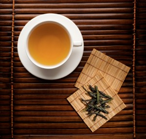 Green tea in a white cup on a dark background