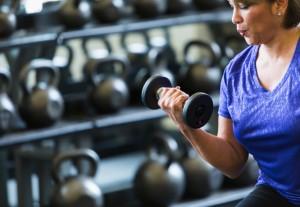 Hispanic woman at gym lifting dumbbell
