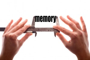 """Color horizontal shot of two hands holding a caliper and measuring the word """"mermory""""."""