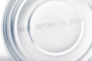 date of expiry canned food close up: letters and numbers of date of best before on silver colored metal aluminium can, tin upside down,