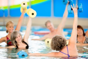 A group of seniors practicing water aerobics in an indoor pool with dumbells, reaching their arms and following the instructor.