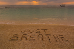 """In the picture a beach at sunset with the words on the sand """"Just breathe""""."""