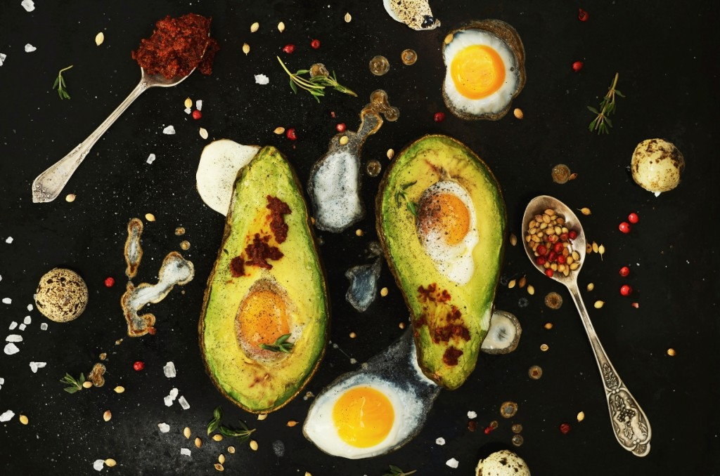 Vibrant picture of grilled avacodo and soft yolk eggs with spoons of spices.