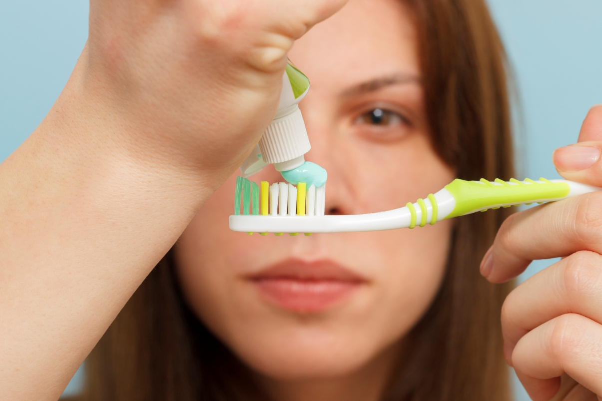 Woman holding tooth brush in front of eyes and applying tooth paste