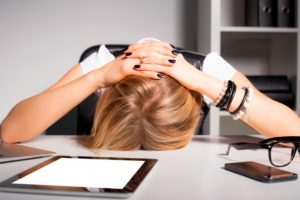 woman with a head ache holding her head on a table