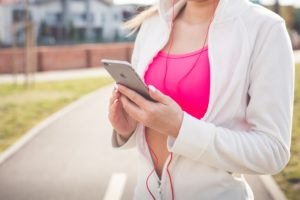 Young woman wearing earbuds and using her phone