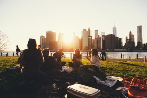 Group of people picknicing in the park with a big city skyline in the background