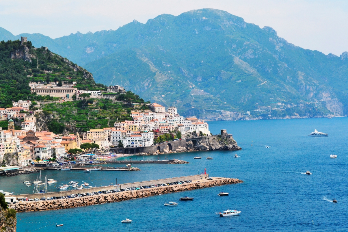 the coast of Acciarolo Italy with boats in the water and mountains in the background