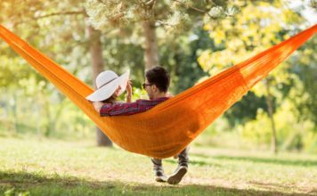 Young man and woman on hammock in green nature from back