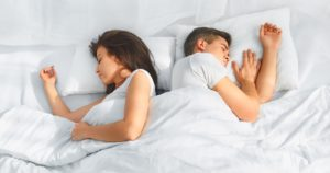 man and woman sleeping in a bed with white bedding
