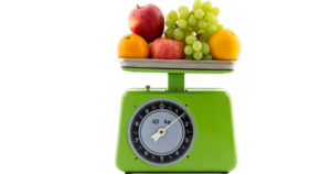 green vintage kitchen scale with oranges, apples and white grapes