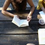 three people study at a wooden picnic table