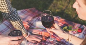 married man and women drinking red wine on a picnic blanket