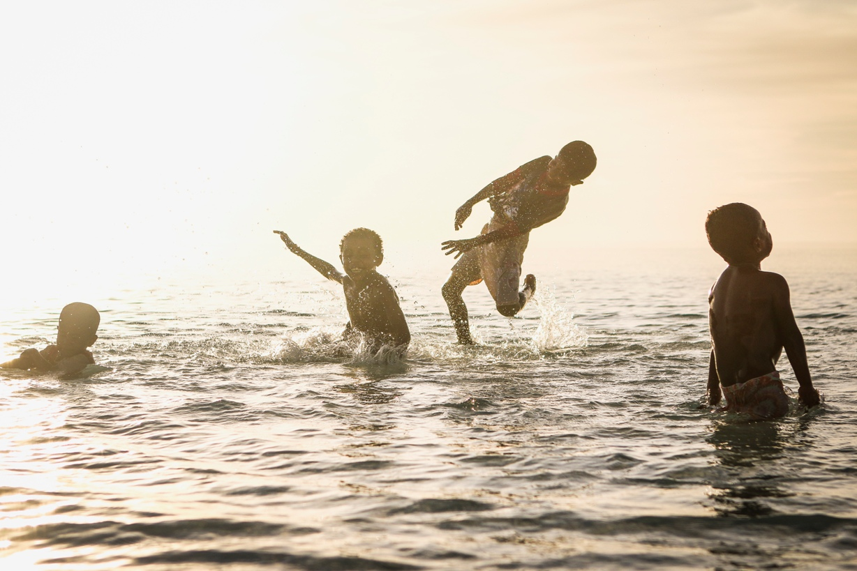 children playing in the sea at sunset