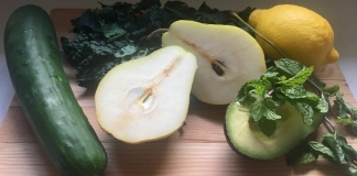 cutting board with cucumber, pear, avacado, lemon, and herbs