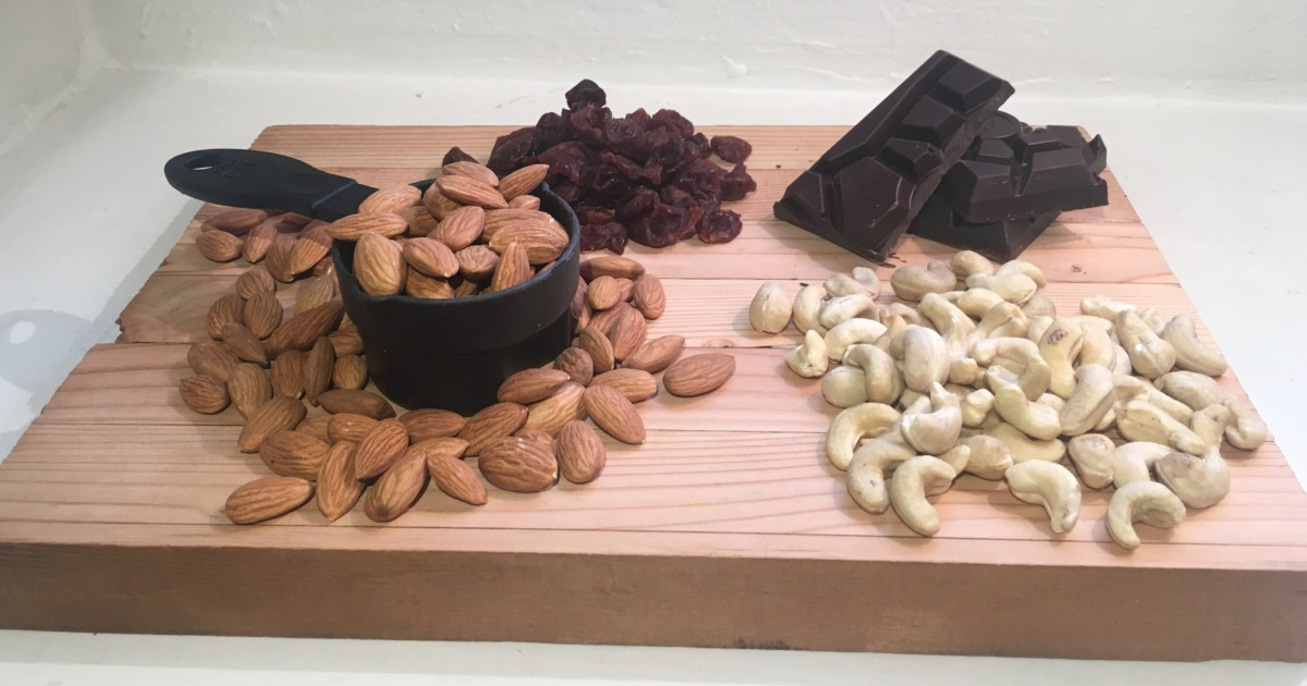 cutting board with dates, chocolate, and nuts