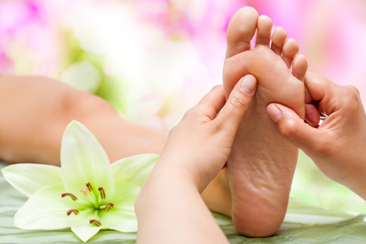 Close up of theraspist's hands massaging female foot.