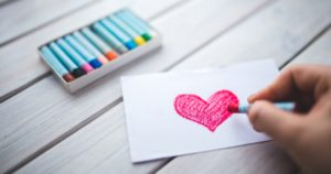 red heart drawn on paper with pastels and pastels in the background.