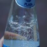 hand holding a bottle of sparkling water