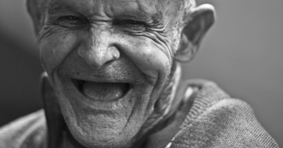 black and white image of elderly man laughing