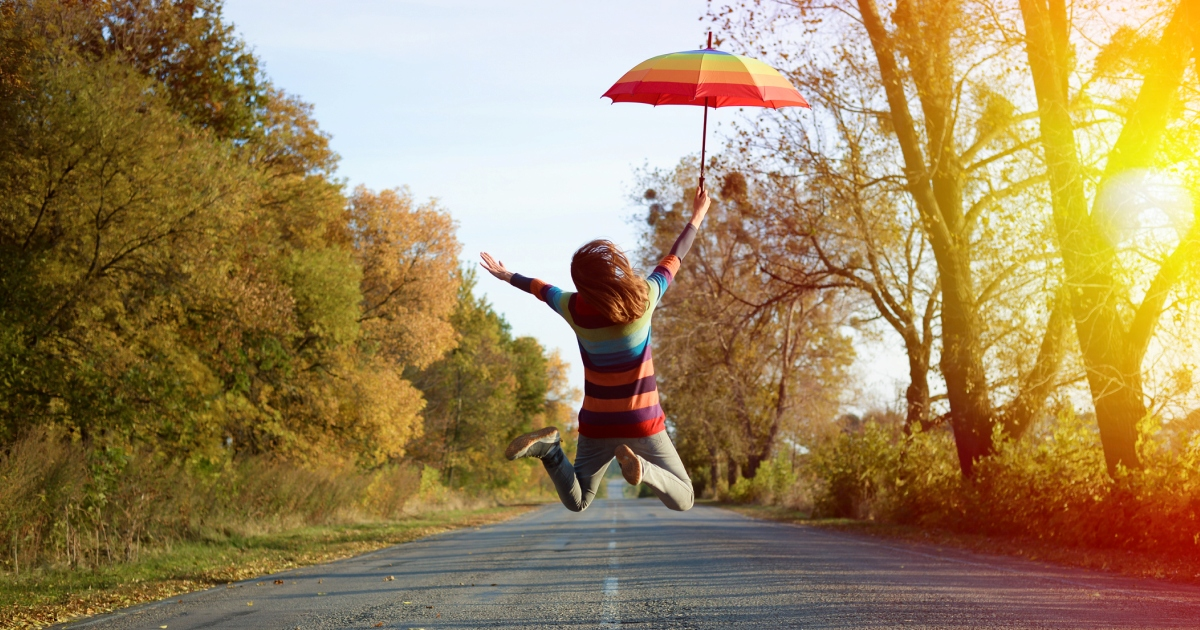 Girl holding a colorful umbrella and jumping for joy