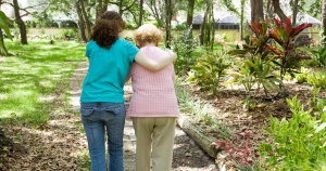 young woman helping an older woman walk