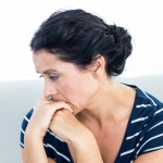 anxious looking woman leaning on her folded hands