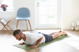 Shot of a handsome mature man doing yoga at home