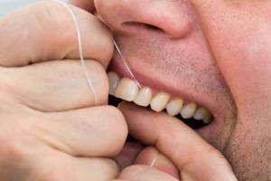 Close-up Of A Man Flossing His Teeth