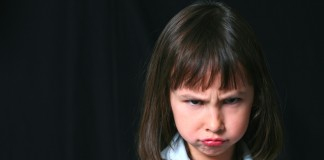 pretty little brunette girl on black background frowning