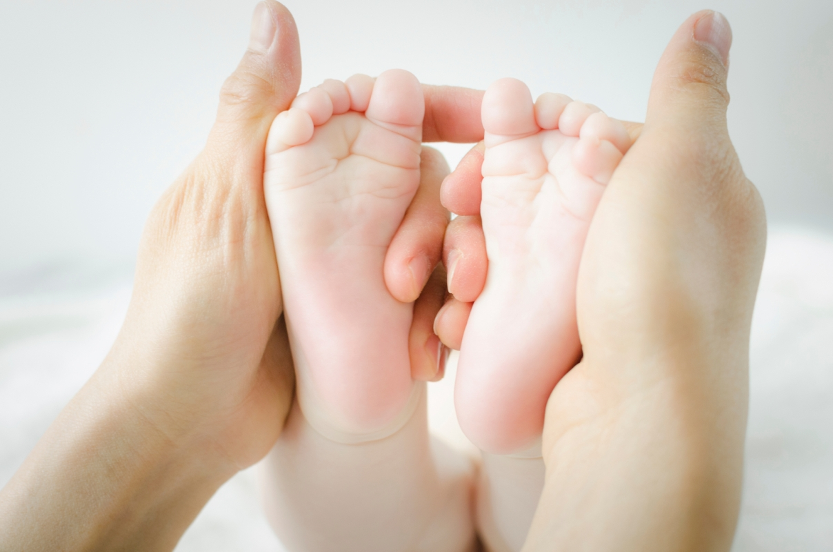 mother's hands holding baby's feet - white background