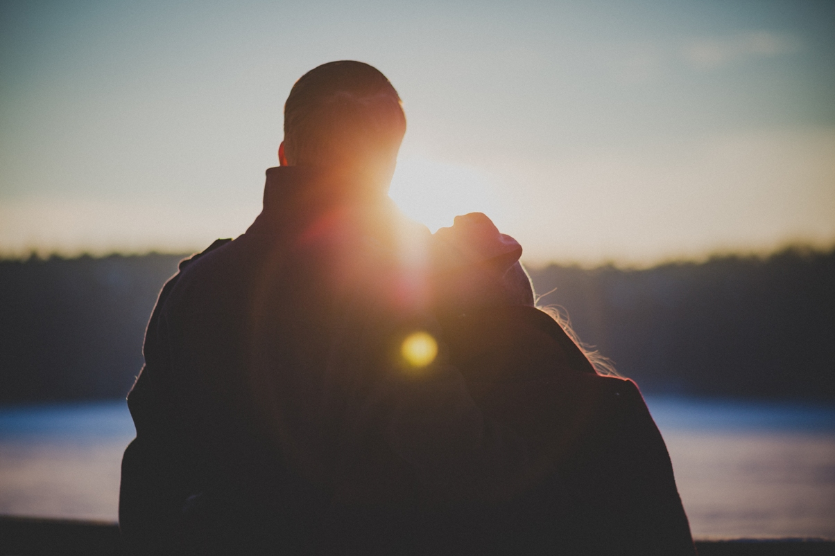silhouette of couple embracing with sunlight shining through