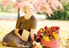 Happy woman sitting on a blanket in the park with baskets of apples and fall flowers