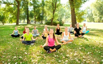 group of young people doing yoga in park