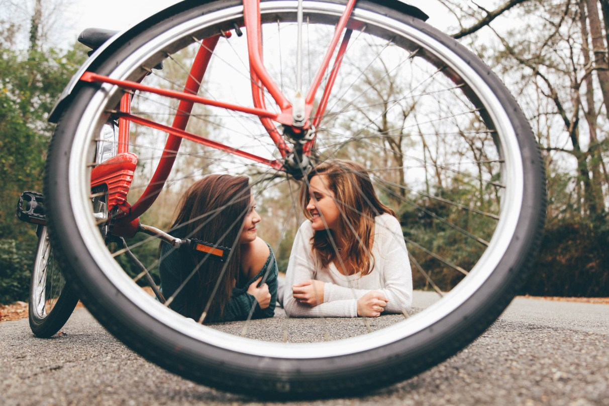 Two girls laying prone and talking seen through the spokes of a bicycle tire