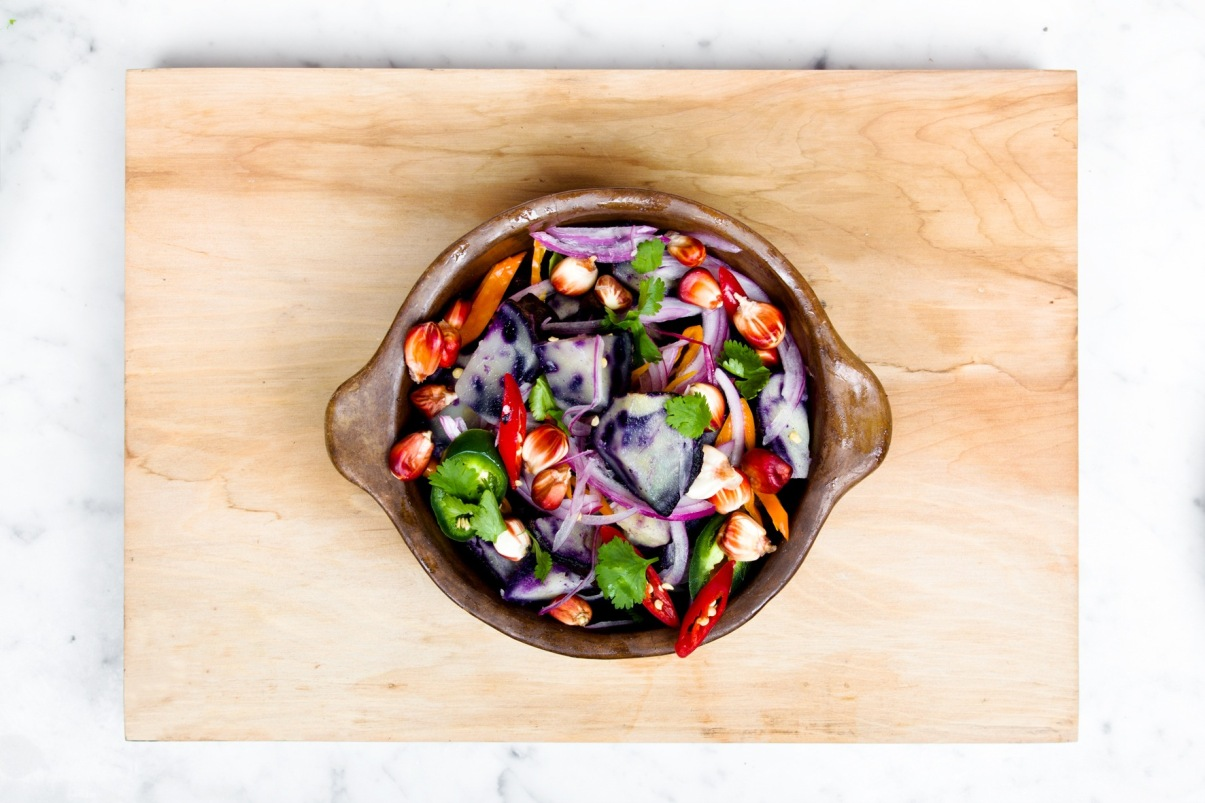 vibrant salad in a brown stoneware dish on a cutting board