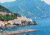 Coast of Acciarolo Italy with boats in the water and mountains in the background