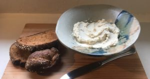wooden cutting board topped with toast and a bowl of vegan cashew cream cheese substitute