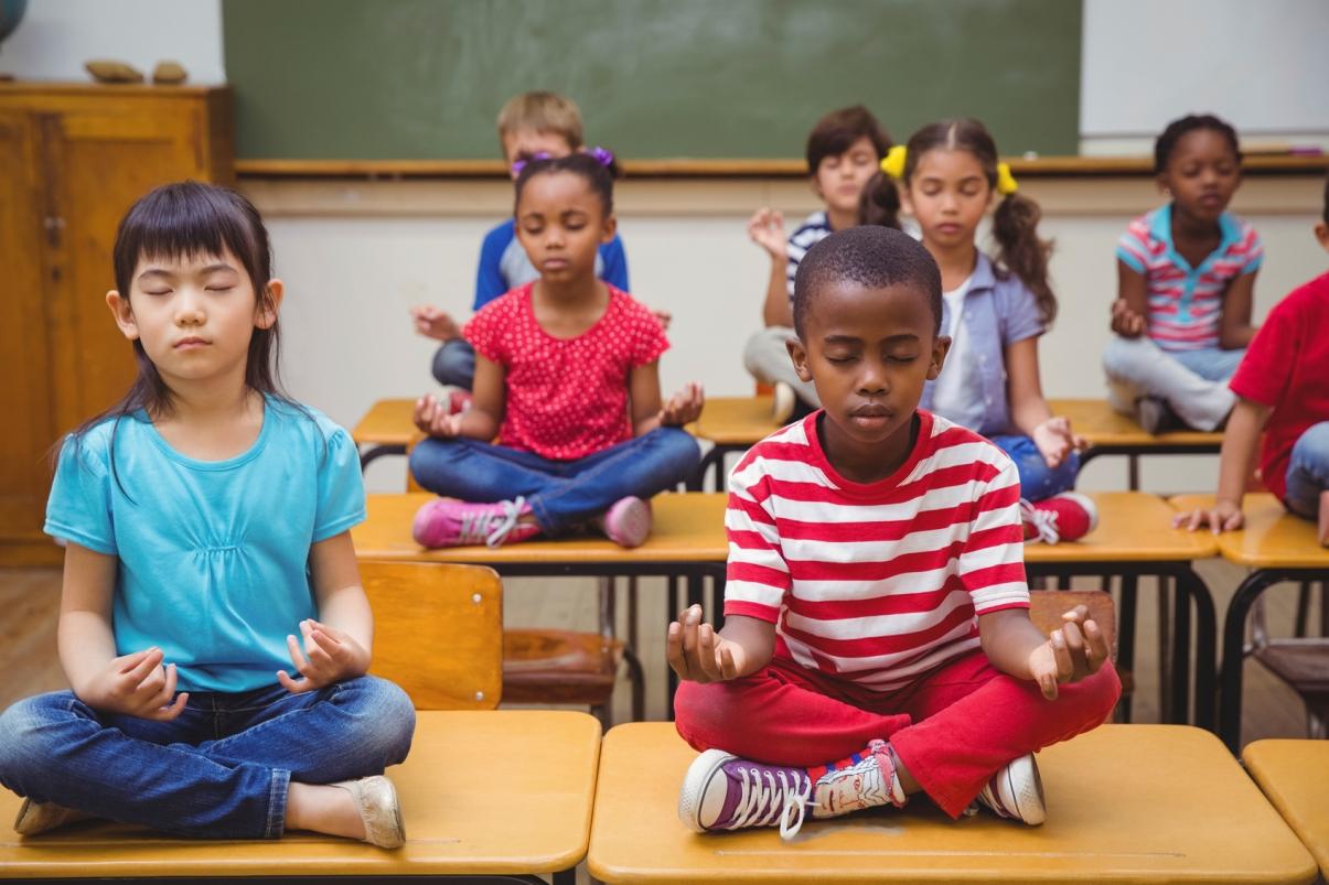 children sitting on top of their desks meditating
