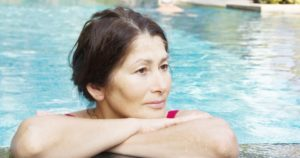 Woman in pool with folded arms resting on edge of pool
