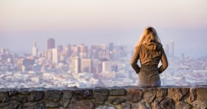 Woman sitting on a rock wall looking over the city