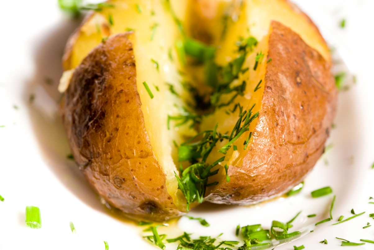 baked potato split down the middle with butter and chives