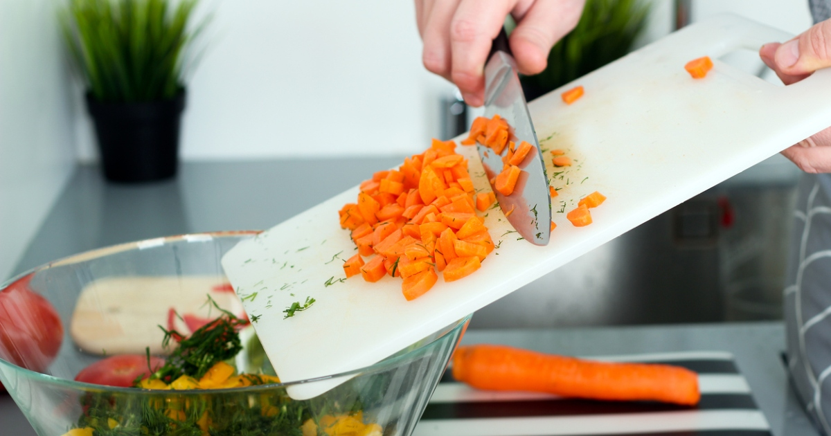 carrots being swept off a cutting board into a bowel of vegetables