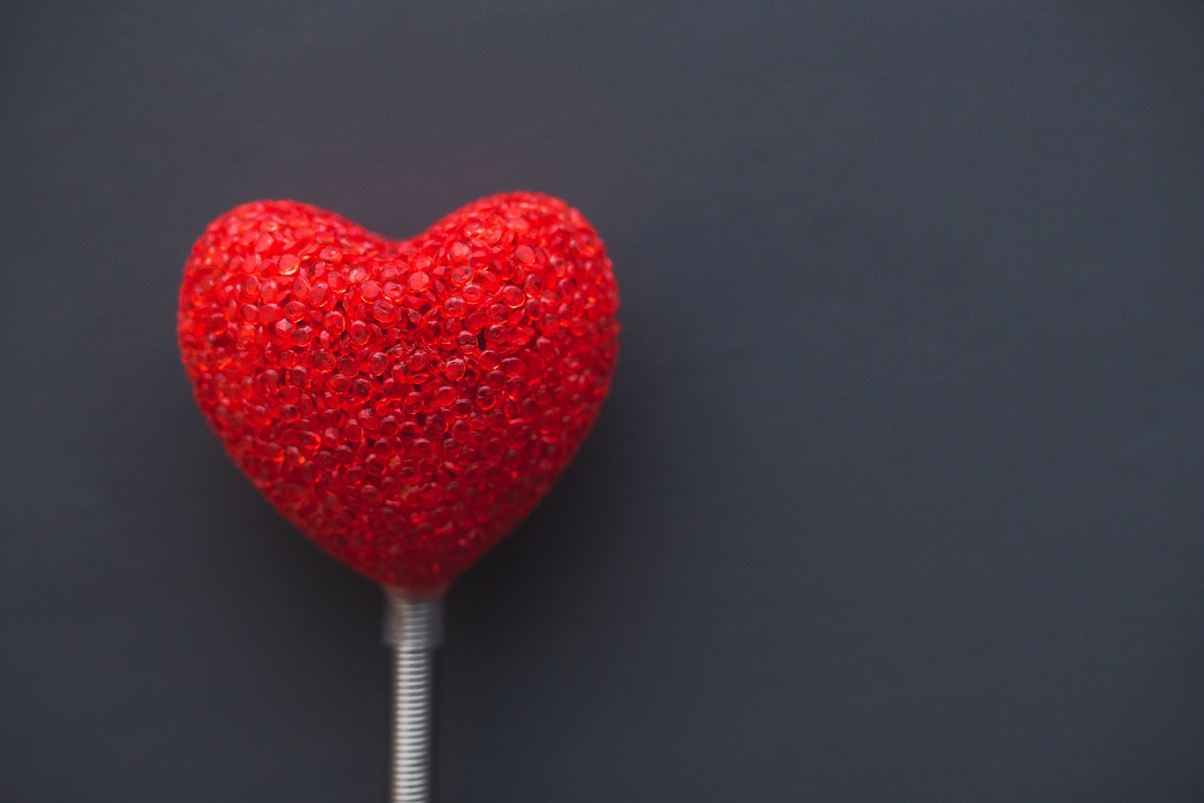 red plastic heart on a white stick with a gray background