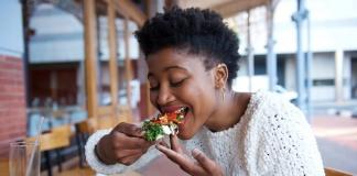 black woman taking a bite of vegan food