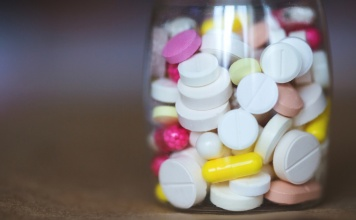 clear bottle filled with aspirin pills