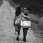 black and white image of a boy and girl walking down a dirt road