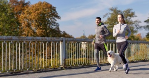 man and woman running with their dog
