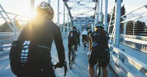 5 people cycling across a bridge