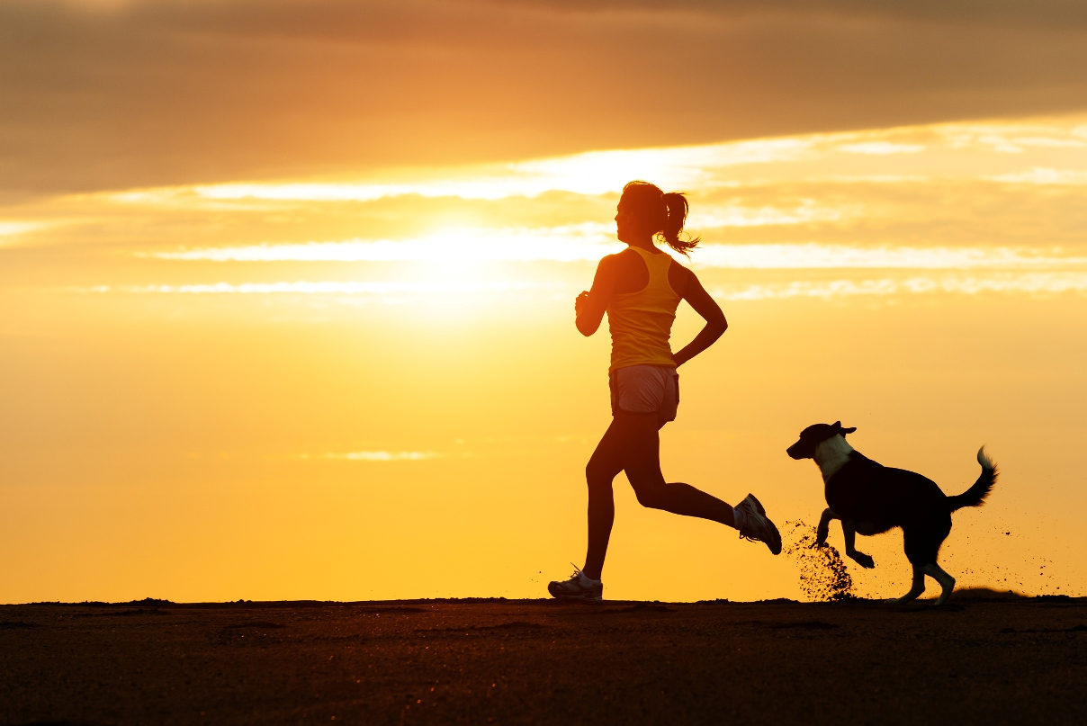woman running with her dog at sunset